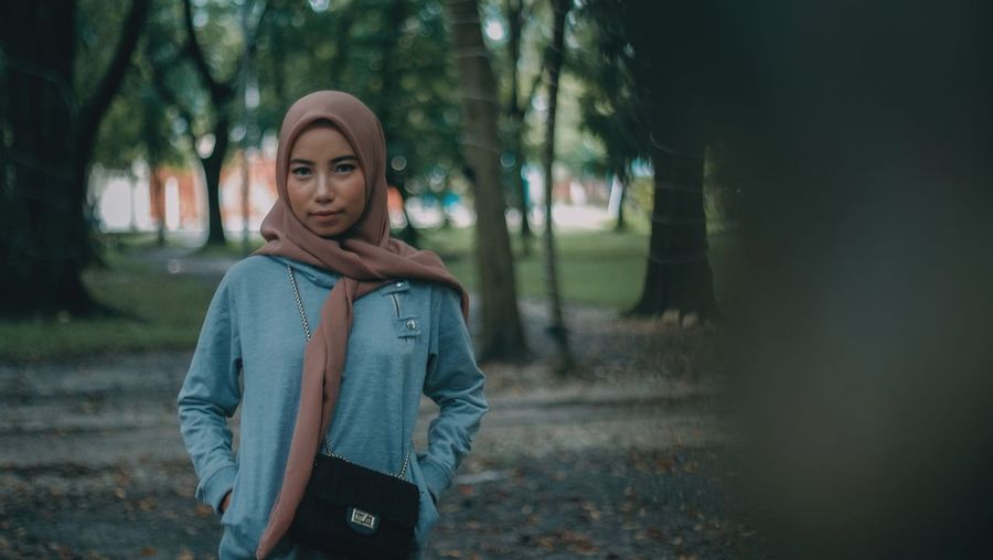 Portrait of young woman wearing hijab while standing at park