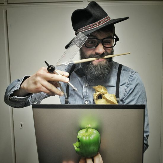 Painter With Painting Equipment And Bell Pepper Against Wall