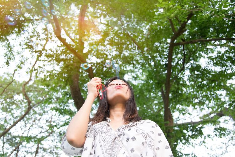 Low angle view of woman blowing bubbles against trees