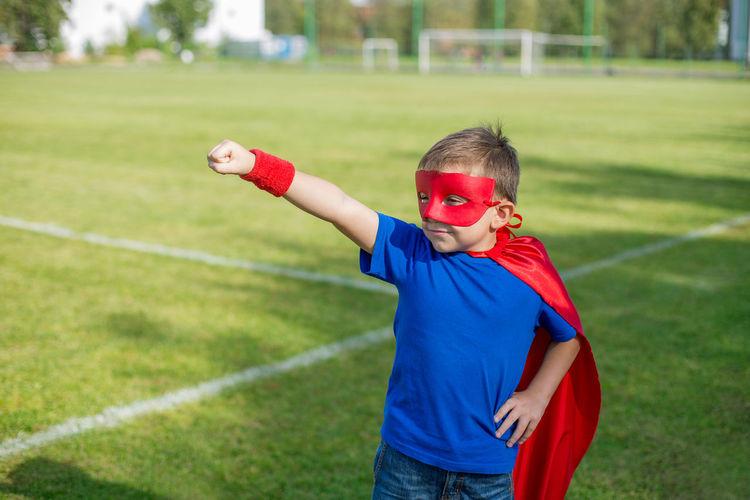 Boy in superman costume standing on field
