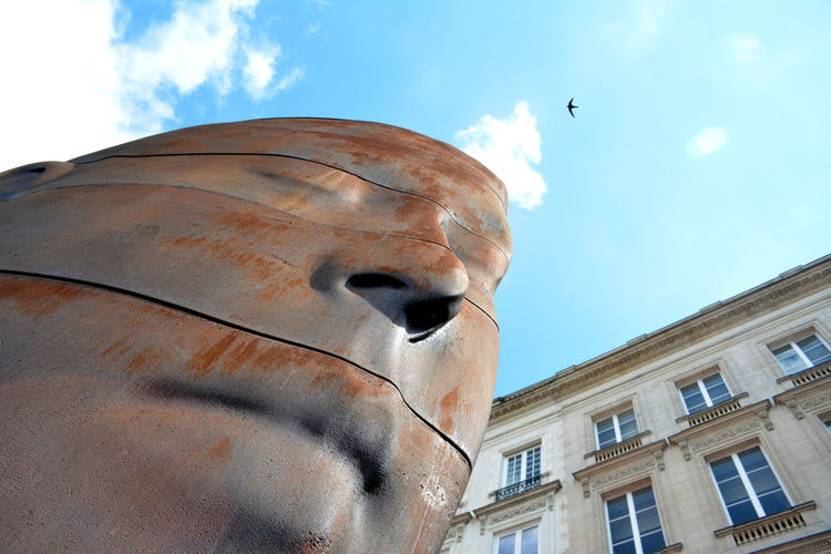 Low angle view of sculpture and building against sky on sunny day