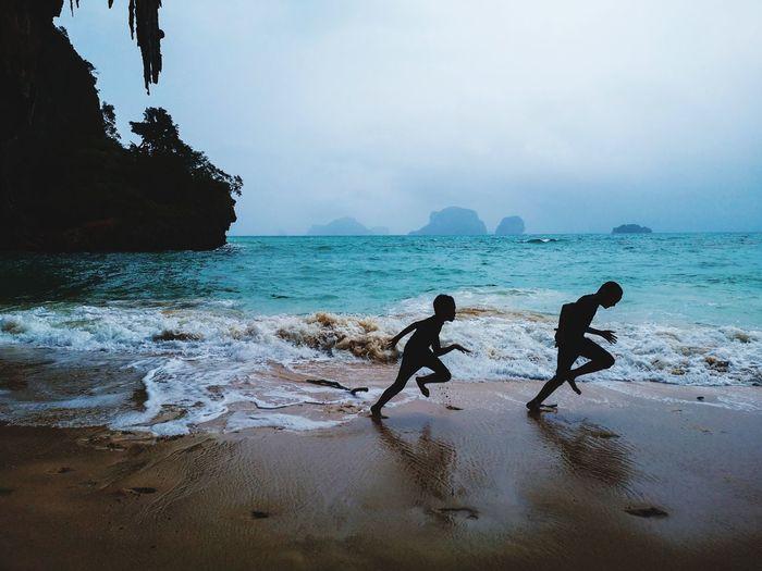 Silhouette Boys Running At Beach Against Cloudy Sky
