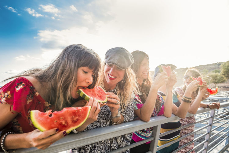 Happy friends eating watermelons by railing against sky