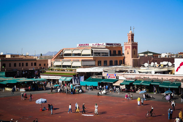 """The Jemaa el-Fnaa is one of the best-known squares in Africa and is the centre of city activity and trade. It has been described as a """"world-famous square"""", """"a metaphorical urban icon, a bridge between the past and the present, the place where (spectacularized) Moroccan tradition encounters modernity."""" Marrakesh, also known by the French spelling Marrakech, is a major city of the Kingdom of Morocco. It is the fourth largest city in the country, after Casablanca, Fez and Tangier. It is the capital city of the mid-southwestern region of Marrakesh-Safi. Located to the north of the foothills of the snow-capped Atlas Mountains, Marrakesh is situated 580 km (360 mi) southwest of Tangier, 327 km (203 mi) southwest of the Moroccan capital of Rabat, 239 km (149 mi) south of Casablanca, and 246 km (153 mi) northeast of Agadir. The ramparts of Marrakesh, which stretch for some 19 kilometres (12 mi) around the medina of the city, were built by the Almoravids in the 12th century as protective fortifications. The walls are made of a distinct orange-red clay and chalk, giving the city its nickname as the """"red city""""; they stand up to 19 feet (5.8 m) high and have 20 gates and 200 towers along them.[90] Bab Agnaou was built in the 12th century during the Almohad dynasty. The Berber name Agnaou, like Gnaoua, refers to people of Sub-Saharan African origin (cf. Akal-n-iguinawen – land of the black). The gate was called Bab al Kohl (the word kohl also meaning """"black"""") or Bab al Qsar (palace gate) in some historical sources. The corner-pieces are embellished with floral decorations. This ornamentation is framed by three panels marked with an inscription from the Quran in Maghrebi script using foliated Kufic letters, which were also used in Al-Andalus. Bab Agnaou was renovated and its opening reduced in size during the rule of sultan Mohammed ben Abdallah. Bab Aghmat is located east of the Jewish and Muslim cemeteries, and is near the tomb of Ali ibn Yusuf.[91] Bab Berrima with its solid """