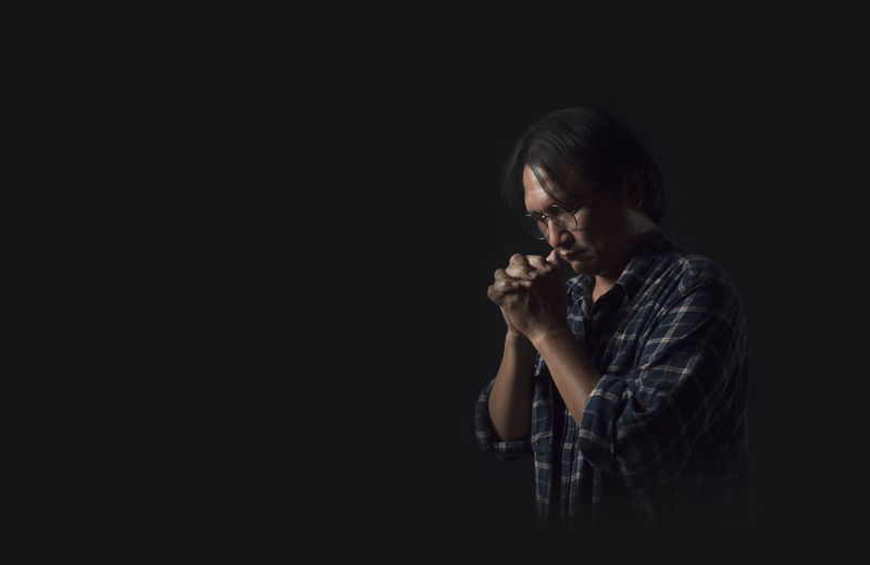 Prayer to God That is the anchor of the mind, faith and hope. Black Background Studio Shot One Person Indoors  Copy Space Young Adult Sadness Adult Looking Emotion Contemplation Waist Up Hand Portrait Cut Out Holding Dark Depression - Sadness Profile View