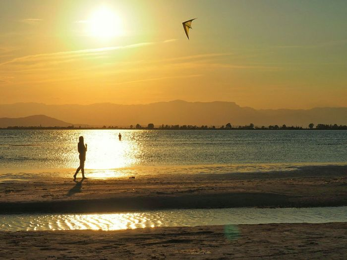 Person flying kite on beach by sea against sky during sunset