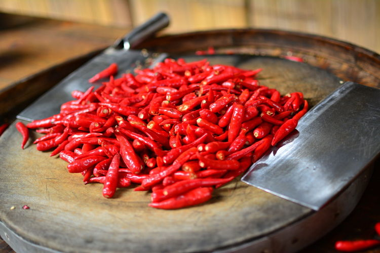 Close-up of red chili peppers with kitchen knives