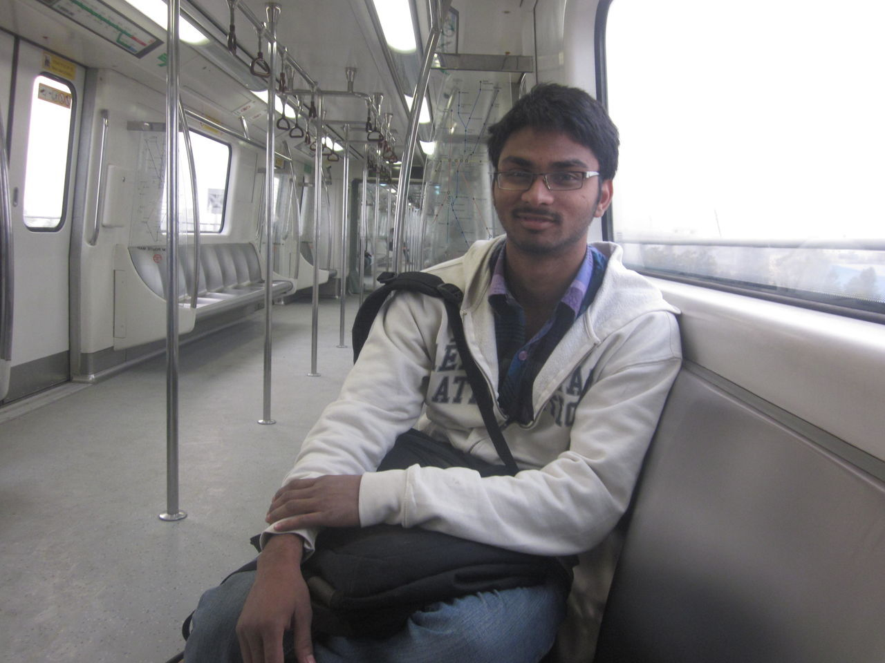 looking at camera, transportation, one person, portrait, public transportation, real people, front view, young adult, young men, sitting, mode of transport, smiling, indoors, vehicle seat, day, people