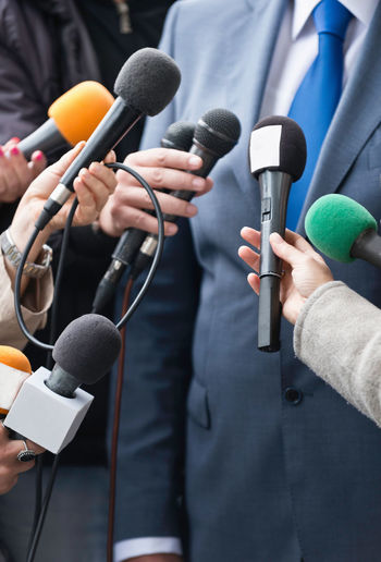 Cropped hands of journalists holding microphones in front of businessman