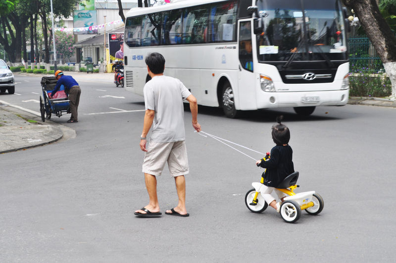 Father towing daughter on toy tricycle in Da Nang street, Vietnam. Buses Childhood Children Coaches Cyclos Da Nang Day Fathers Outdoors Outings  Real People Rear View Road Rope Street Toddlers  Togetherness Towing Transportation Tricycles  Vietnam