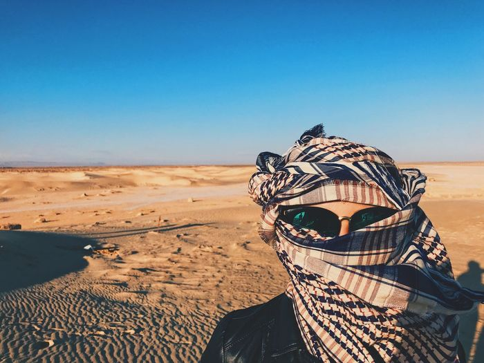 Portrait of woman face covered with scarf in desert against clear sky