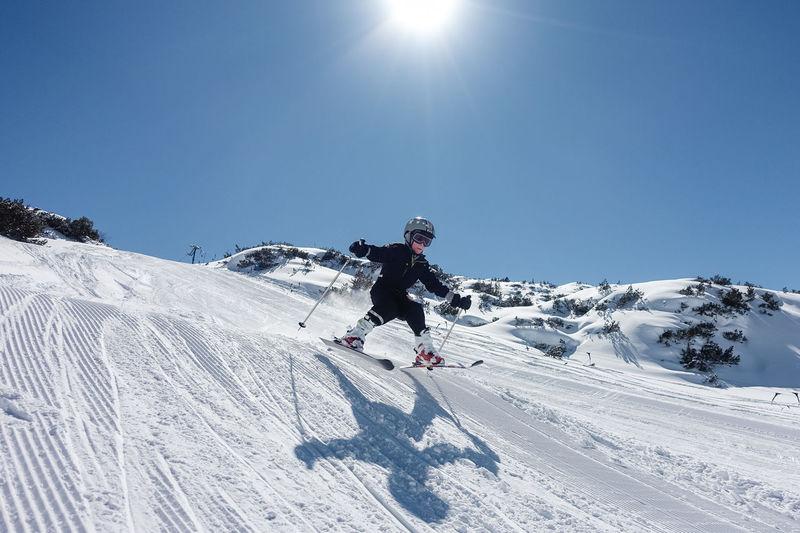 Full Length Of Boy Skiing On Snow Field Against Sky