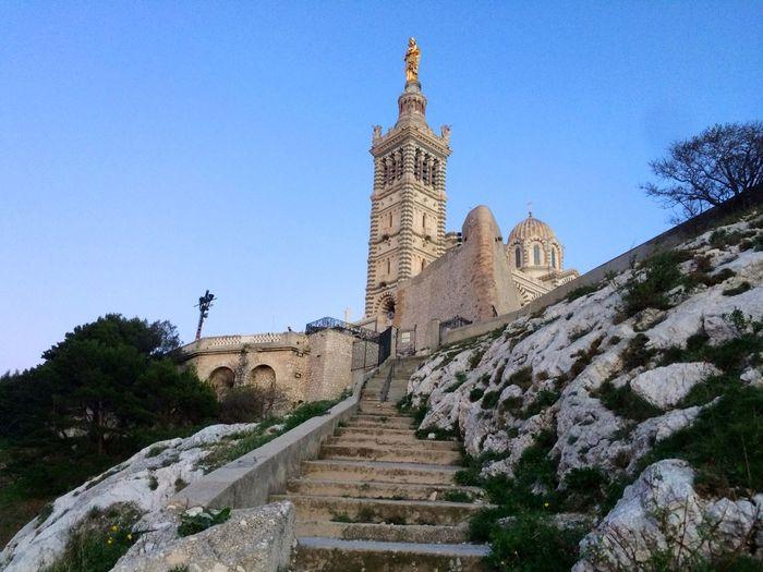 Low angle view of steps leading towards notre-dame de la garde against clear sky