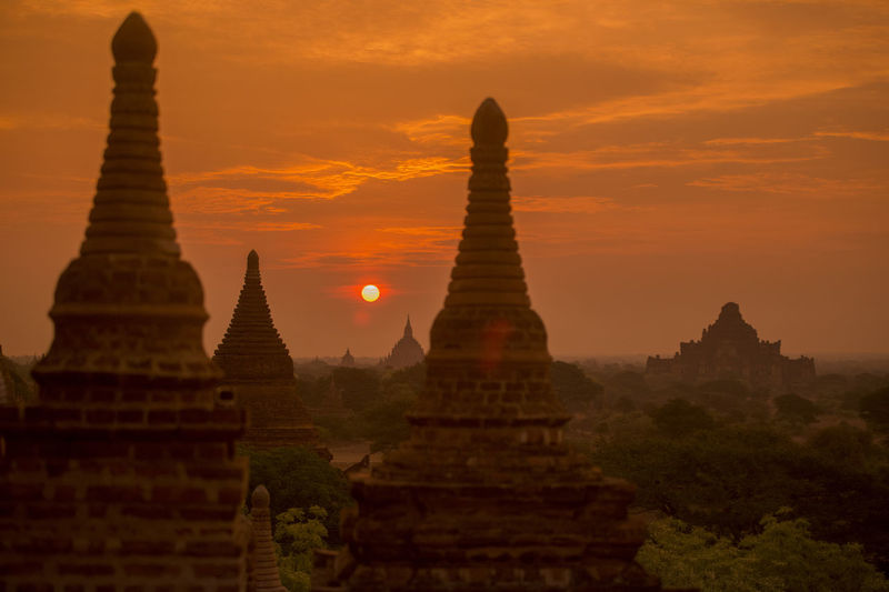Stupas against dramatic sky during sunset