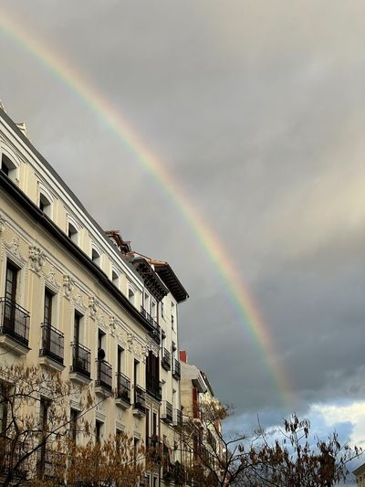 Low angle view of rainbow over buildings against sky