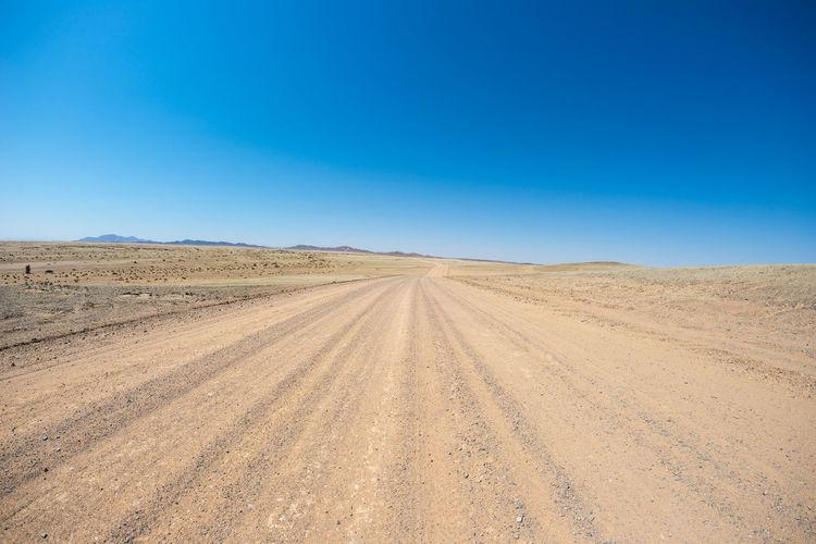 Tire tracks on desert against clear blue sky