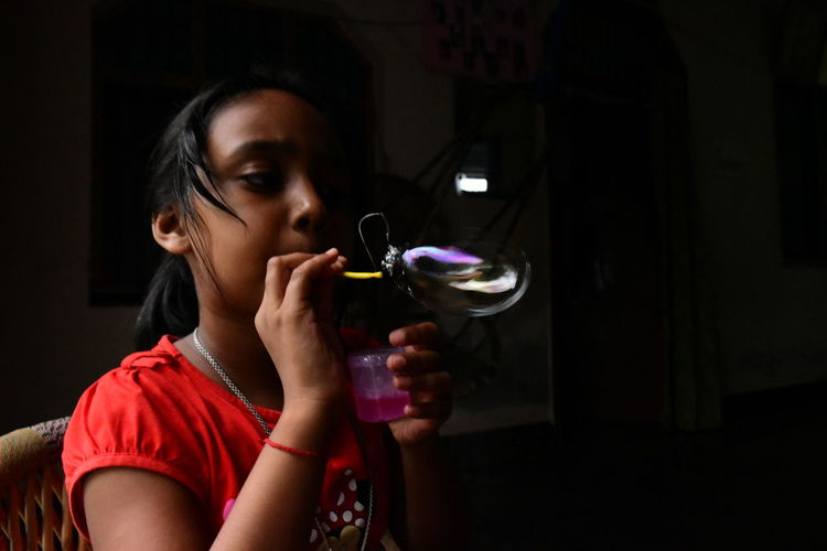 Girl blowing bubbles while sitting at home