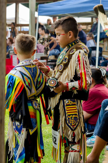 september 3, 2017, two young boys, wear American Indian traditional clothing, or regalia, while waiting to dance in a competition at the Kee-Boon-Mein-Kaa Pow Wow in Dowagiac Michigan USA Pow Wow Traditional Clothing Culture American Indians Children Dance Dowagiac Michigan, USA Boys Clothing Colorfulbeads Competition Decorative Editorial  Kid Male Native American Outdoors Patterns Real People Regalia Vertical Young Adult