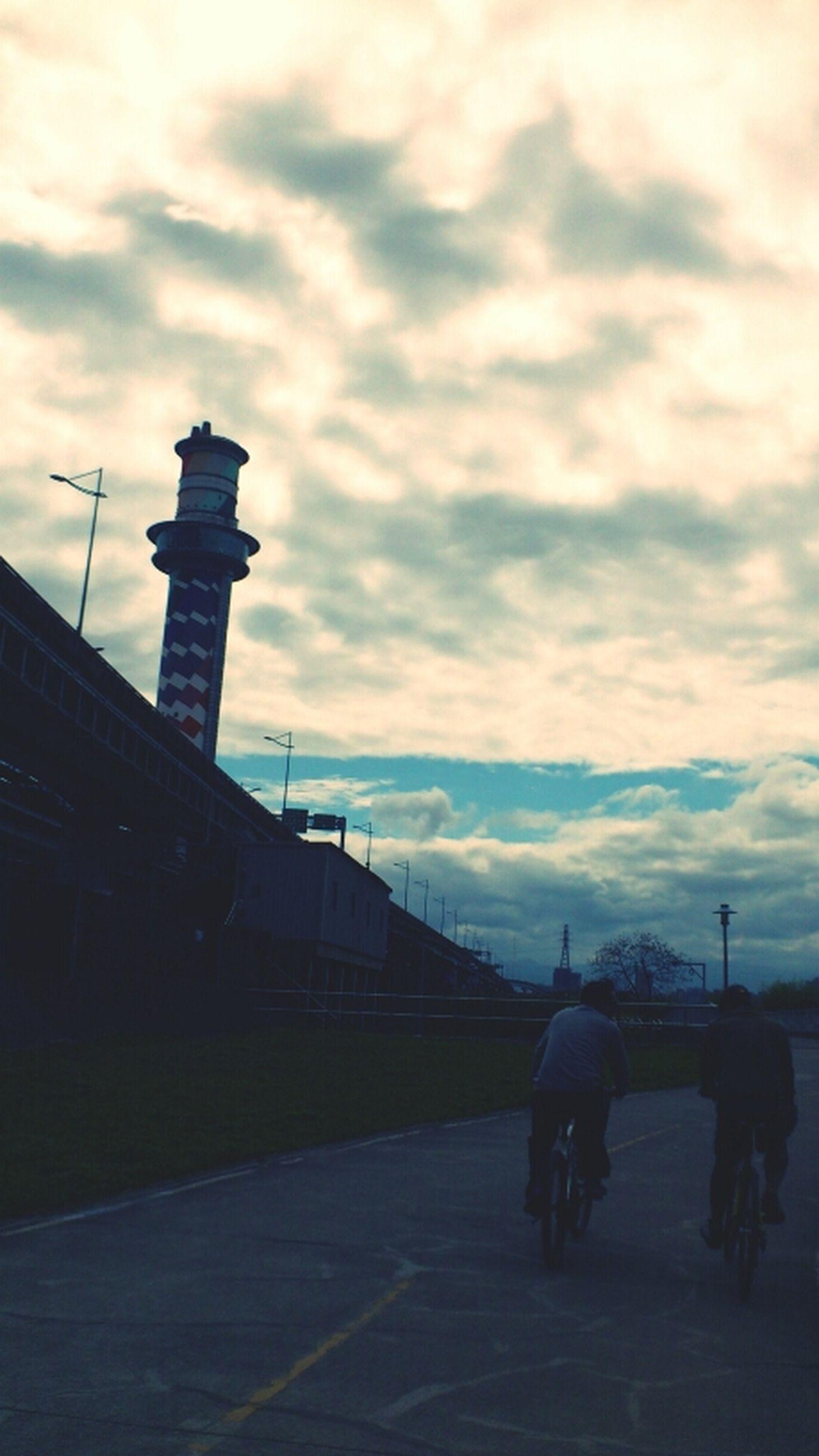 sky, cloud - sky, architecture, built structure, cloudy, building exterior, men, lifestyles, cloud, silhouette, weather, transportation, leisure activity, full length, railing, street light, dusk