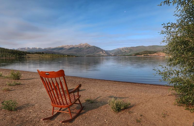 Landscape of lakeshore, mountains in the background and a red rocking chair Rocking Chair Dillon Reservoir Colorado Water Seat Chair Sky Tranquility Beauty In Nature Lake Absence Nature No People Beach Tranquil Scene Scenics - Nature Tree Plant Day Mountain Cloud - Sky Empty Outdoors