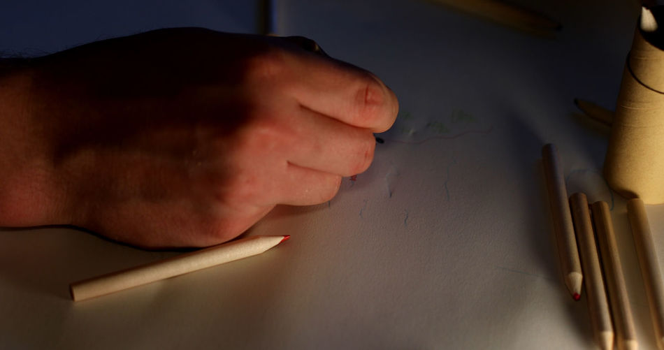 Close-up of hand holding painting on table