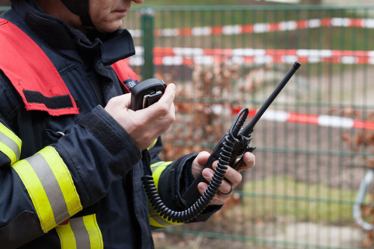 Midsection Of Firefighter Holding Walkie-Talkie