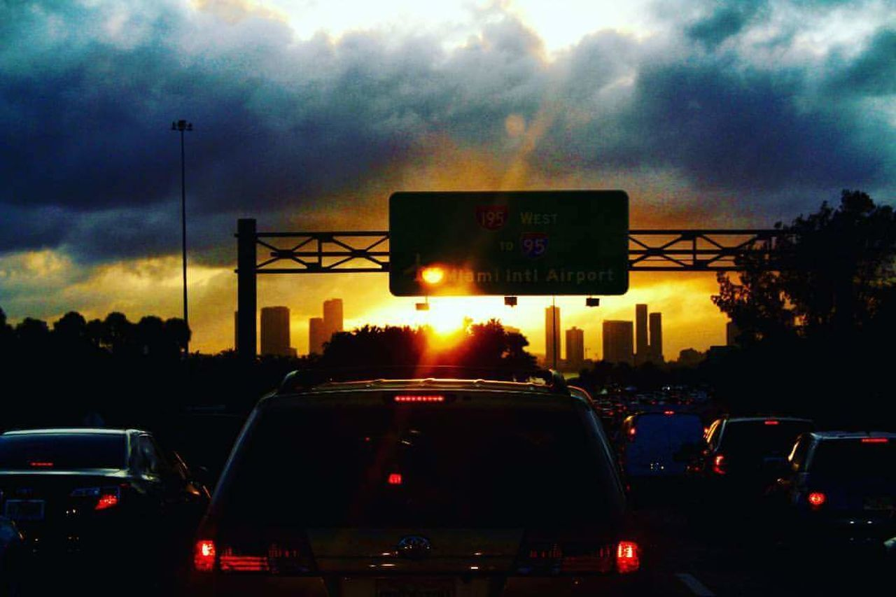 car, transportation, land vehicle, traffic, sunset, sky, cloud - sky, road, red light, illuminated, mode of transport, silhouette, outdoors, road sign, no people, stoplight, rush hour, storm cloud, city, day