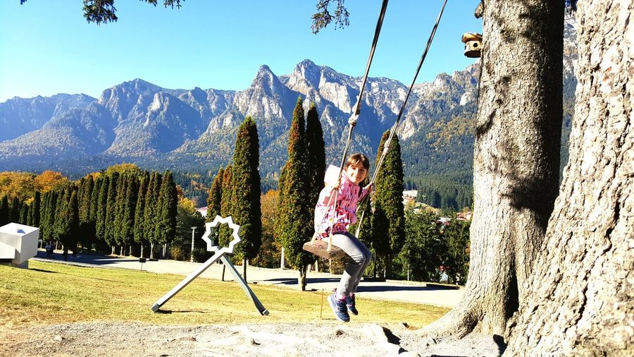 Portrait of smiling girl swinging with mountains in background