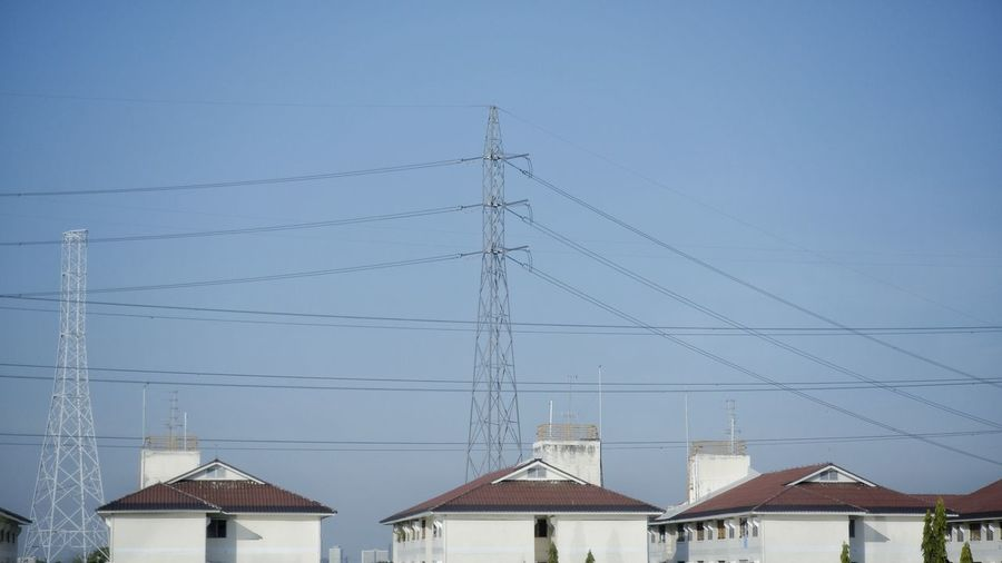 Low angle view of electricity pylon and buildings against clear sky