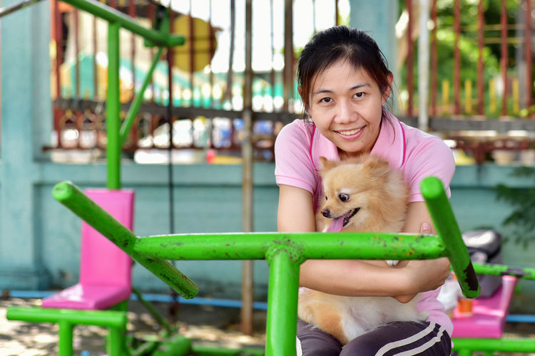 Portrait of woman holding dog sitting outdoors