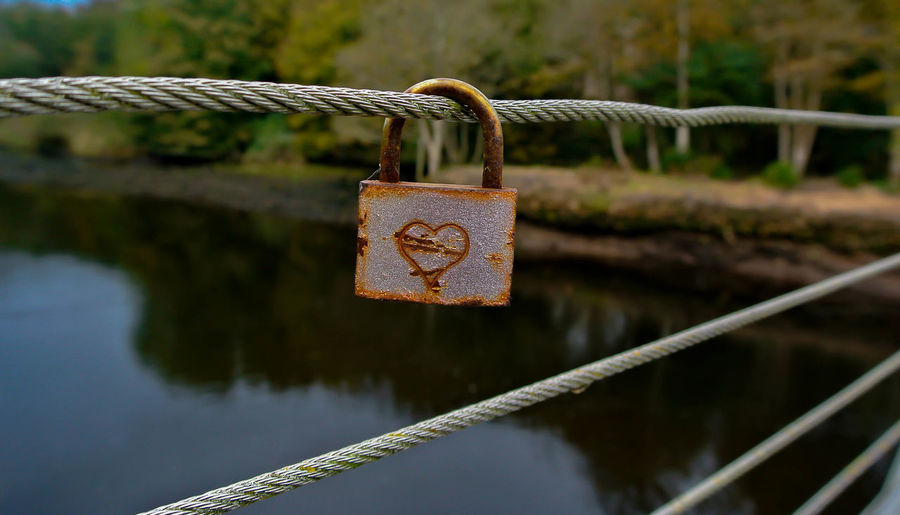 Close-up of padlock on cable against river