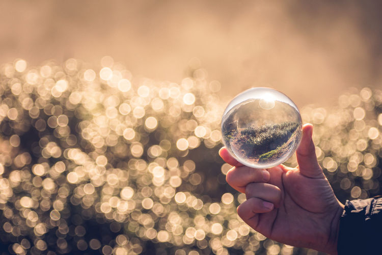 Close-up Crystal Ball Day Focus On Foreground Geometric Shape Glass - Material Hand Holding Human Body Part Human Hand Nature One Person Outdoors Reflection Shape Sky Sphere Sunlight Transparent