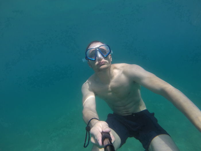 Shirtless man taking selfie in sea