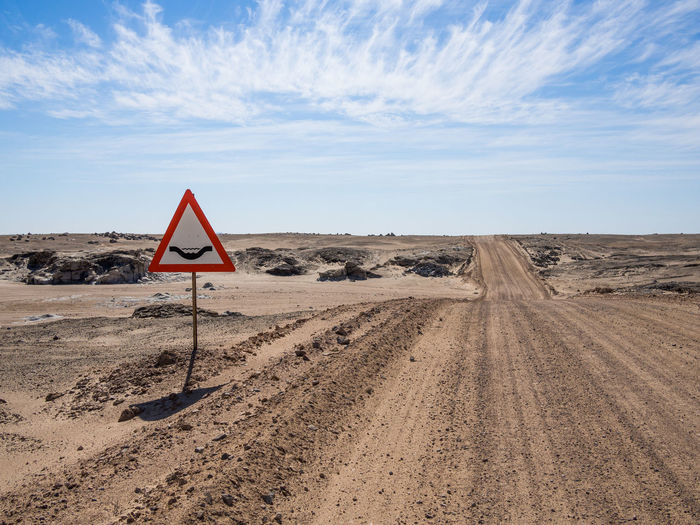 Road sign of river crossing in namib desert against sky, namibia