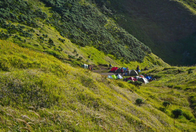 People by tent on field against mountain