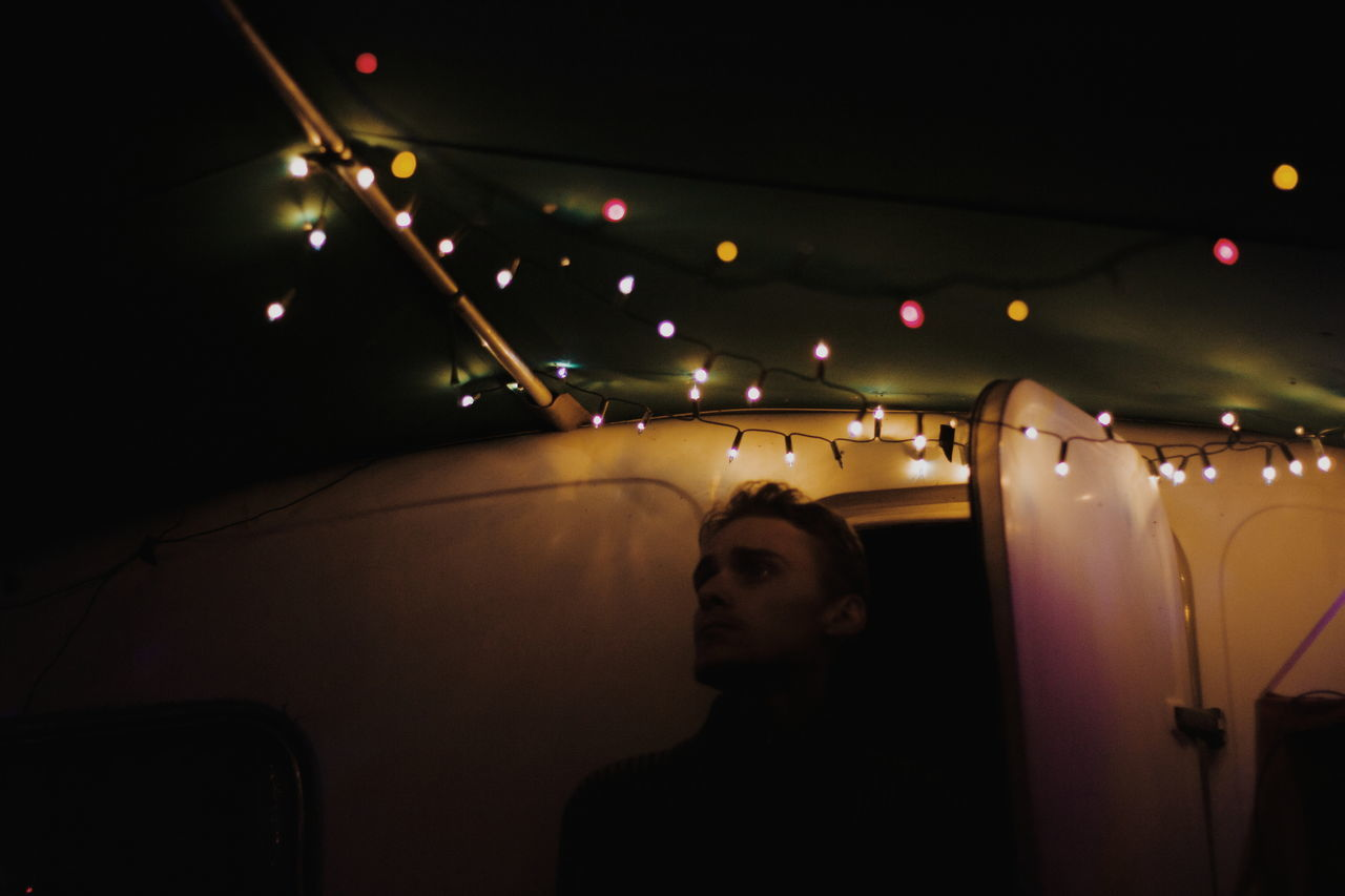 Man looking away while standing at entrance of illuminated motor home