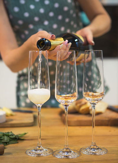 Midsection of woman pouring champagne in flutes on table