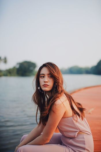 Woman looking away while sitting by river