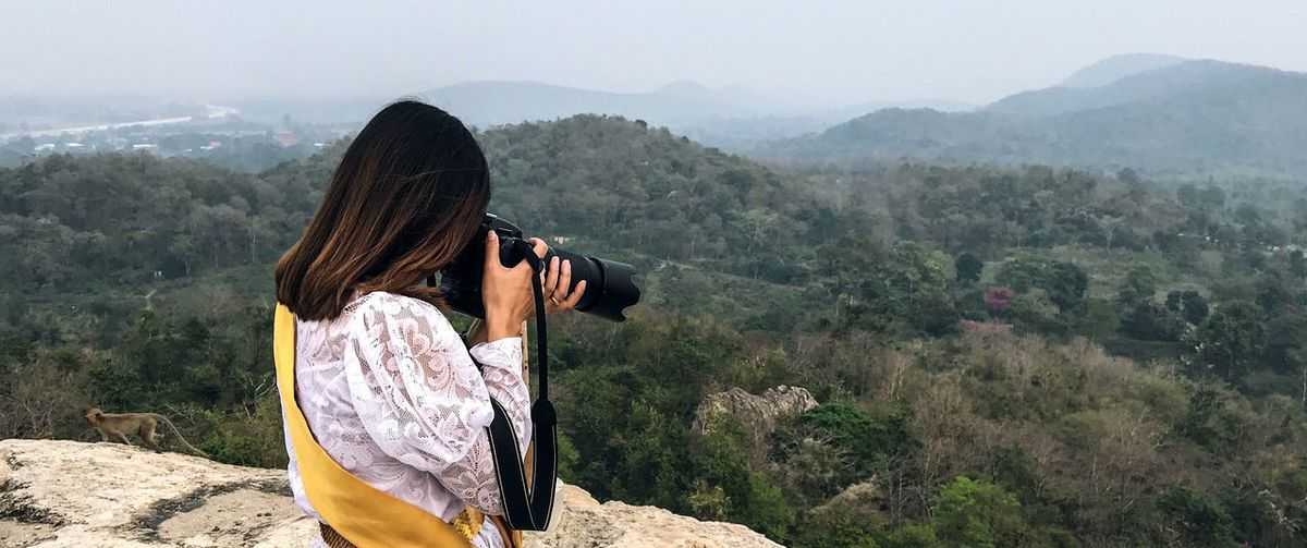 Woman photographing standing against landscape
