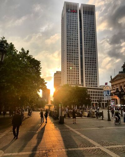 Architecture Sky Built Structure Building Exterior Crowd Large Group Of People City Office Building Exterior City Life Sunset Tall - High Group Of People Cloud - Sky Tree Plant Real People Men Street