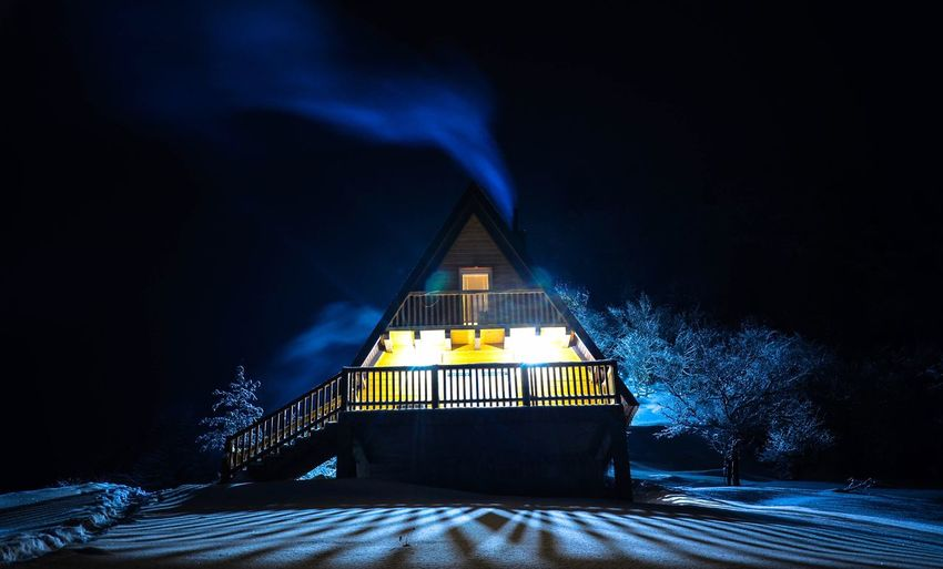 Illuminated built structure in winter at night