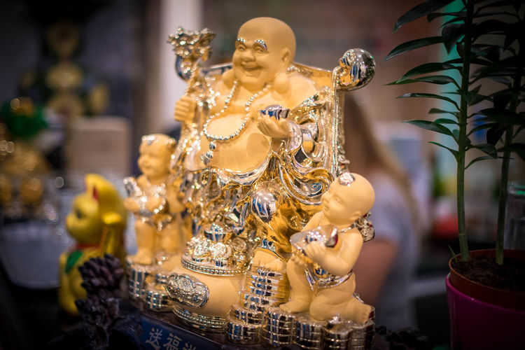 Art And Craft Budai Close-up Craft Creativity Female Likeness Figurine  Focus On Foreground Gold Colored Human Representation Idol Indoors  Male Likeness No People Representation Retail  Retail Display Sale Sculpture Spirituality Statue Store