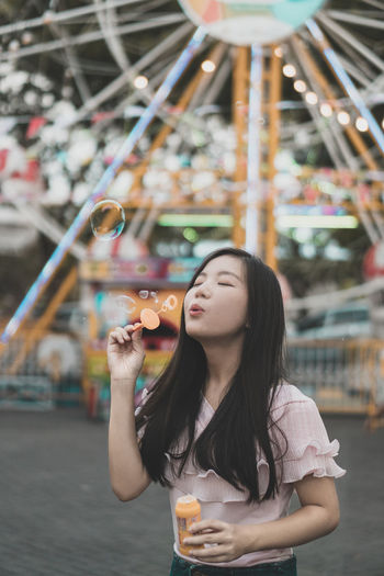 Young woman holding bubbles in amusement park