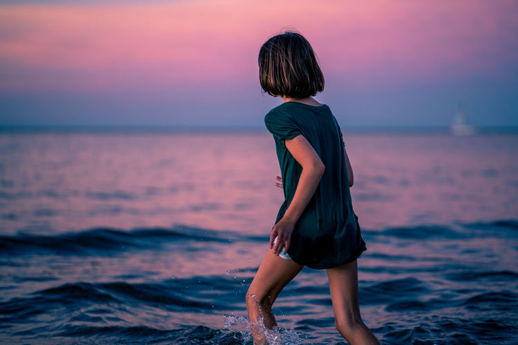 Rear view of woman standing on beach during sunset