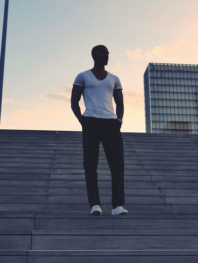 Low angle view of man standing on steps against sky during sunset