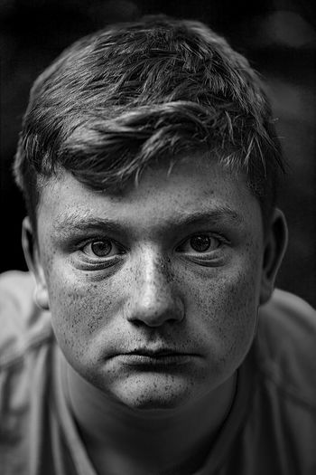 Close-up portrait of teenage boy with freckles
