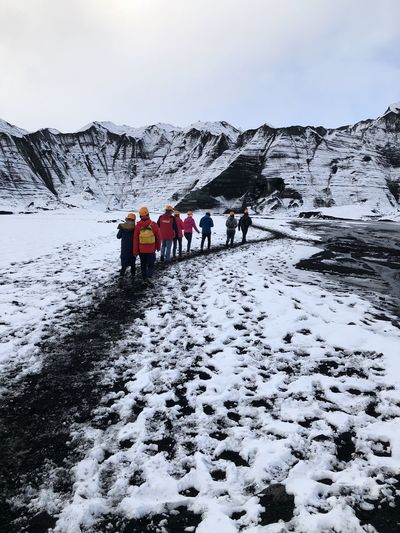 Rear view of people walking on snowcapped mountain against sky