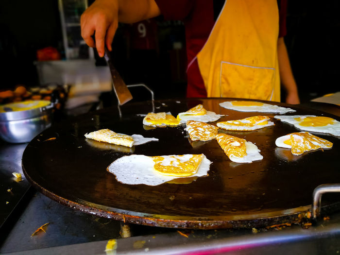 A restaurant worker is making fried eggs on a large skillet. Food Cooking Market For Sale Hand Indian Food Street Food Malaysia Food And Drink Handmade Foodphotography Asian Food Curry Foodporn Market Stall Eggs Benedict Fry Street Market Apron Cooked Alfresco Vendor Wok Eggs... Eggs For Breakfast Market Vendor Stall Frying Pan Skillet- Cooking Pan Freshness Real People Indoors  Preparation  Ready-to-eat Midsection People Unrecognizable Person Healthy Eating Preparing Food Kitchen Utensil Table Close-up Holding Wellbeing Heat - Temperature Incidental People Fried Temptation Snack