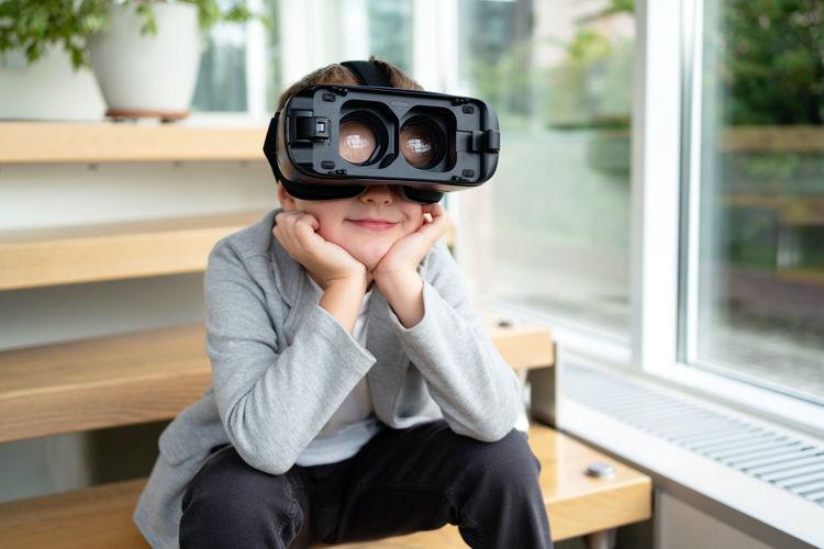 Portrait of boy holding camera while sitting on window