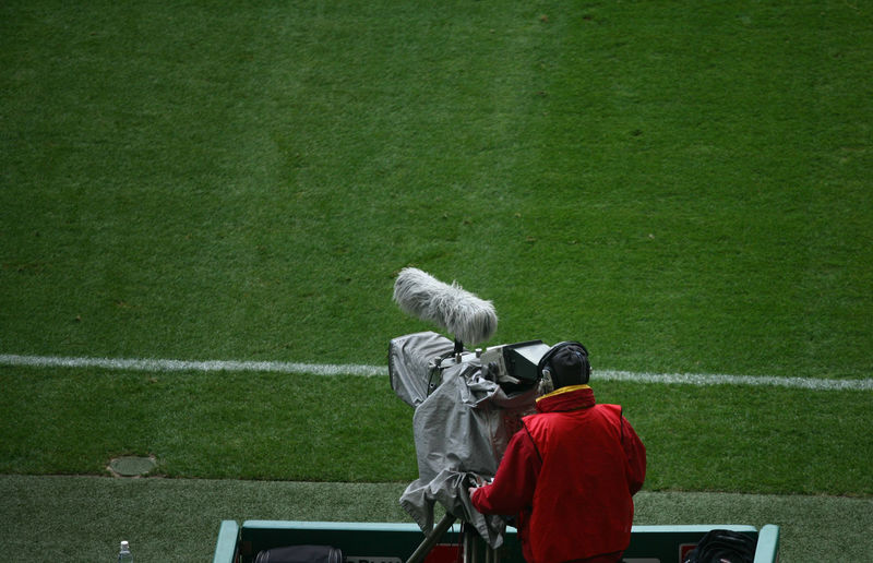Rear view of man with television camera on sports field